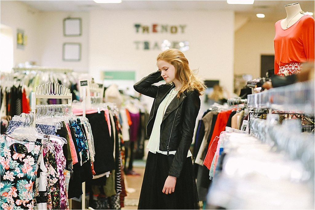 teen model fixing her hair in the aisle of trendy trade resale clothing shop