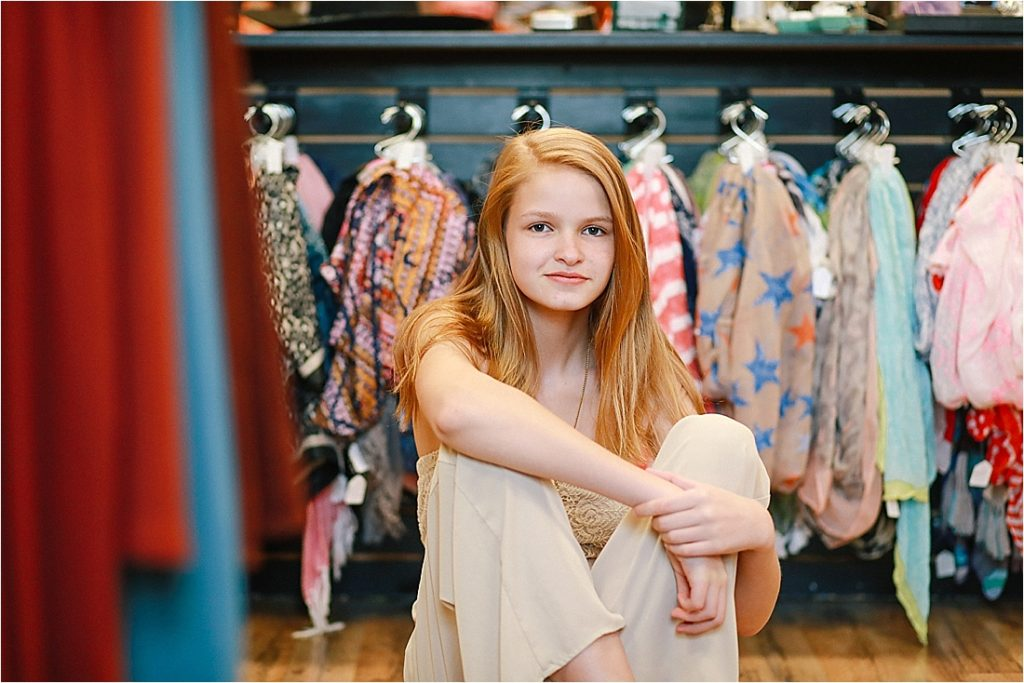 teen sitting in front of scarves for sale at trendy trades in homer city pa small town