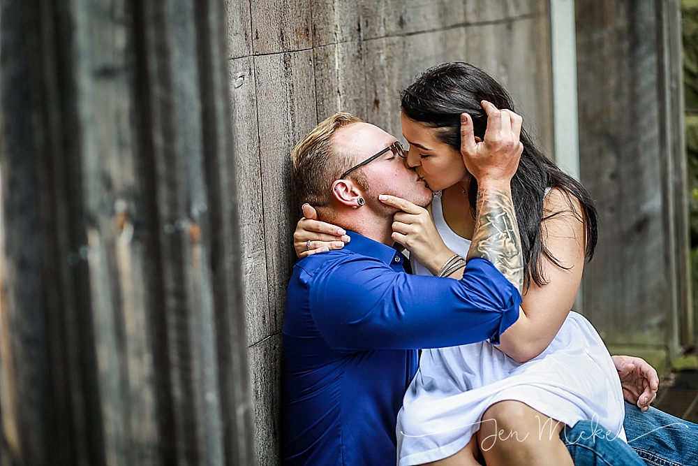 kissing in front of a barn door in a rustic engagement photo session in blairsville pa