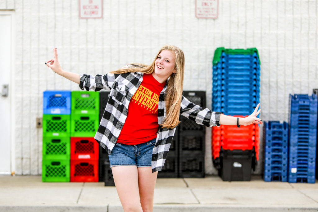 teen giving the peace sign in front of plastic milk crates