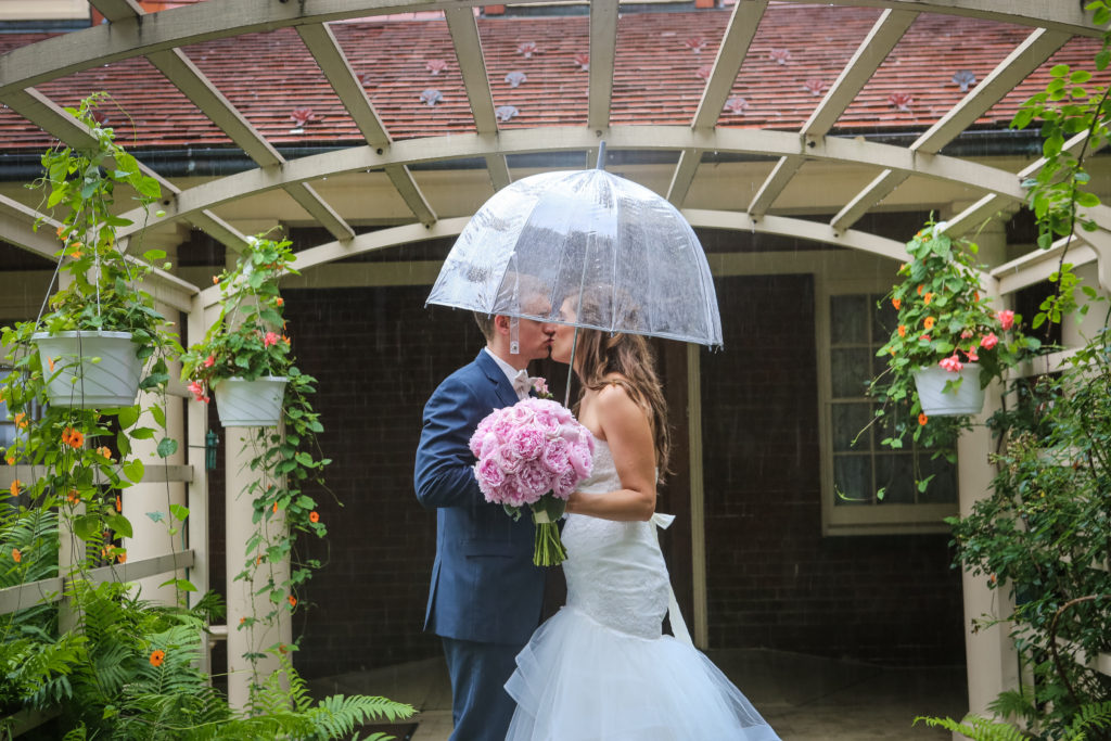bride and groom huddle under a clear umbrella when it rained on their wedding day
