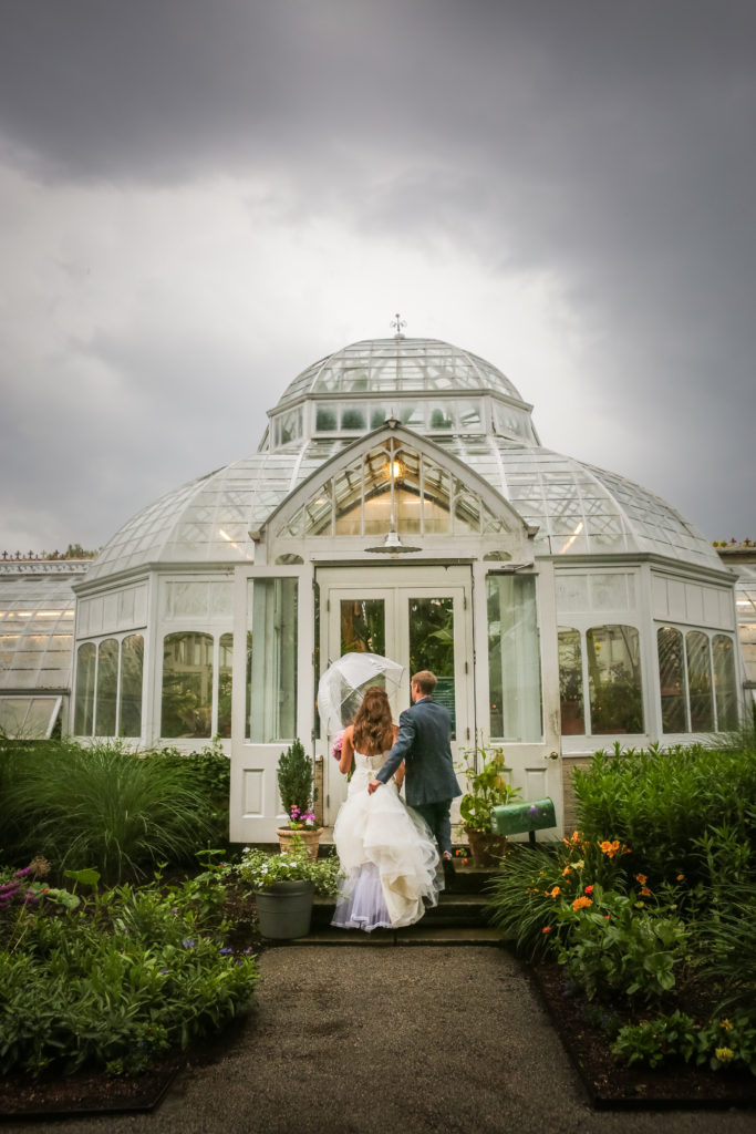 bride and groom rushing into green house on a rainy day wedding