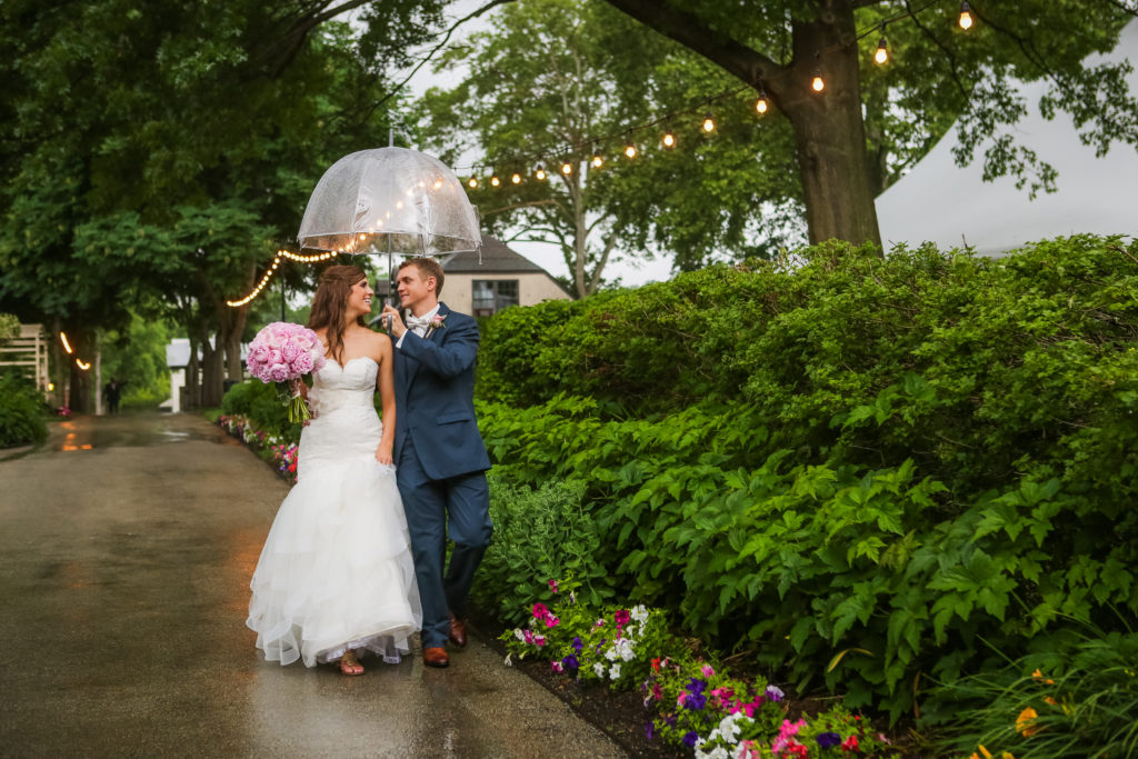 bride and groom walking in the rain under a clear umbrella
