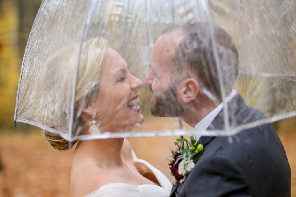 bride and groom kiss under a clear umbrella when it rains on their wedding day