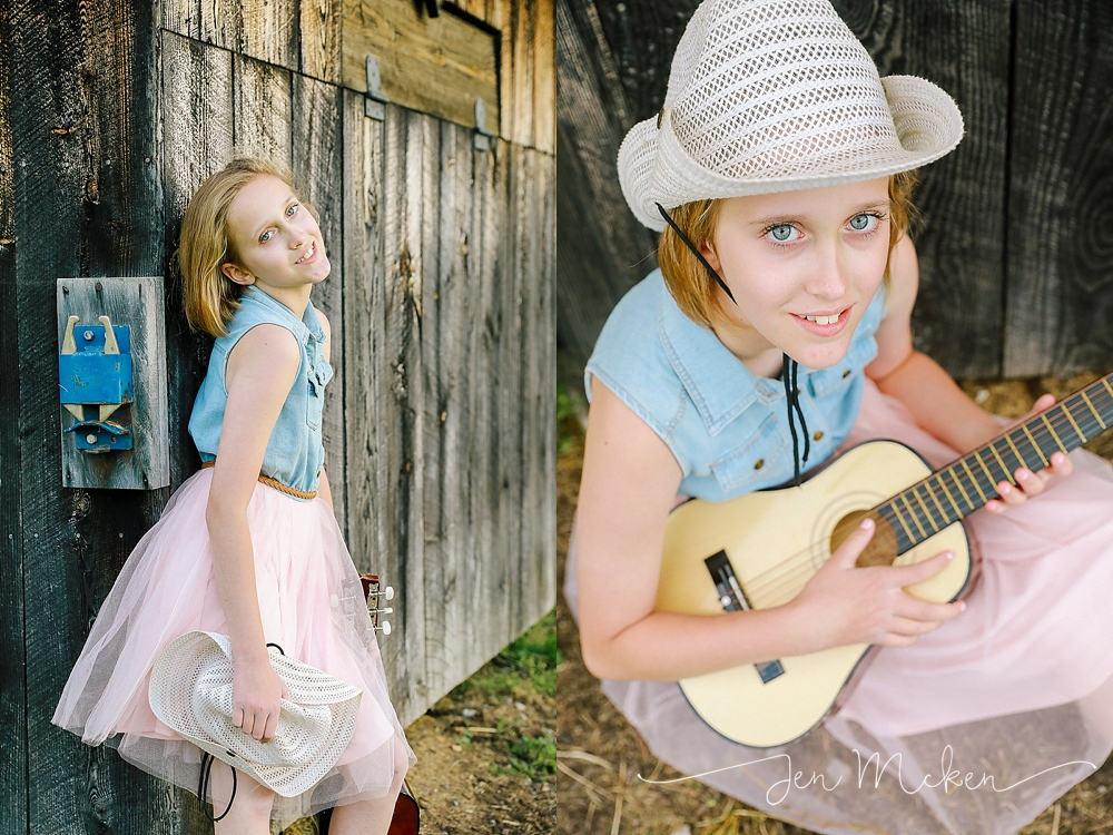 teen girl plays guitar wearing her cowboy hat in front of a barn