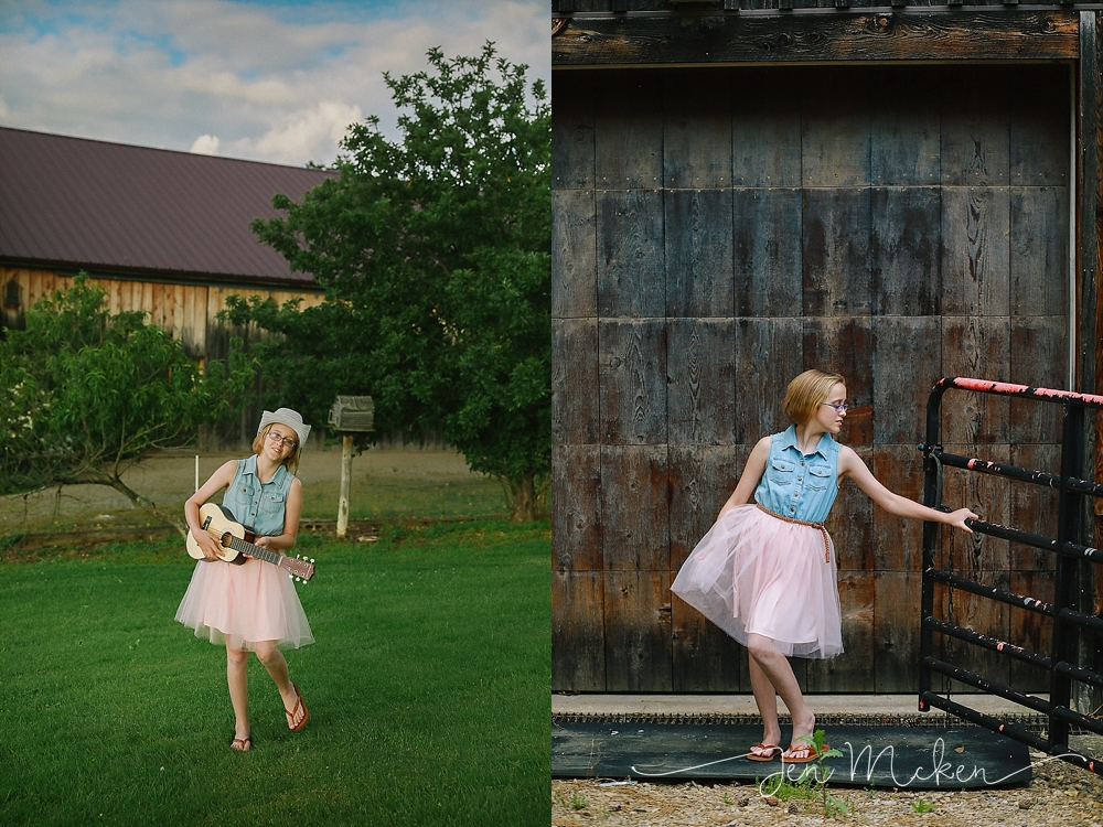 tween dresses up in front of a barn whlie playin the guitar in a small town