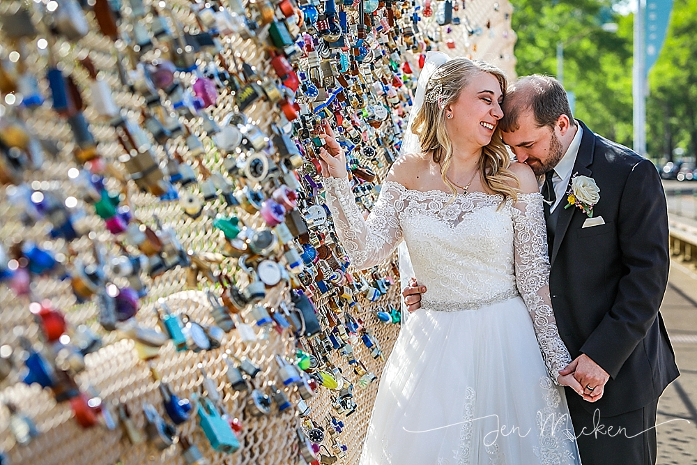 bride and groom place their lock on pittburgh's lock bridge in schenley park