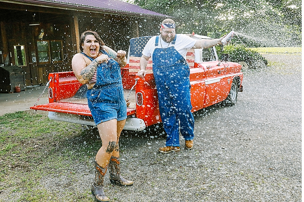 spraying beer can in front of a 1965 chevy pickup wearing blue denim suspenders and an american flag bandana