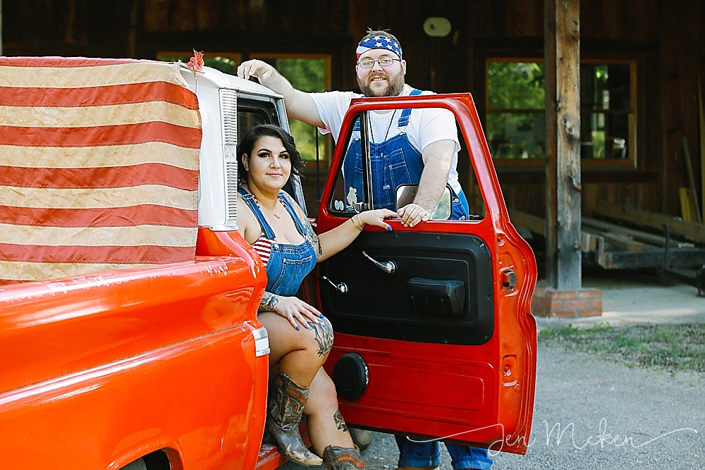couple posing with the 1965 red chevy wearing suspeners and a bandana
