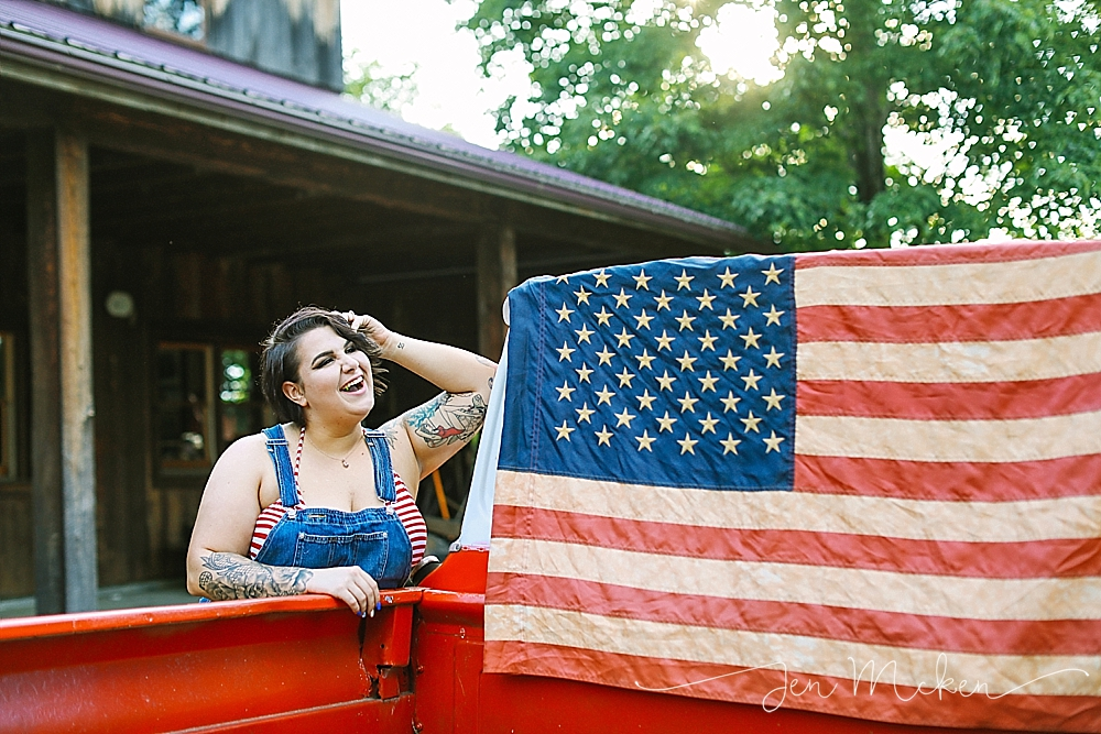 Girl laughing and posing in front of the american flag