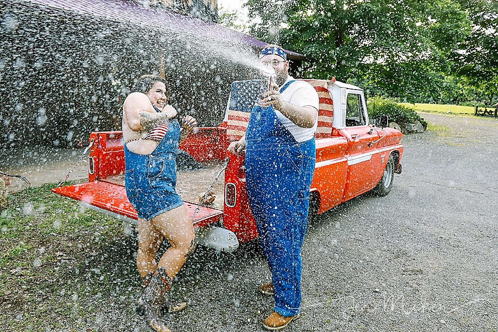 spraying beer can in front of a 1965 chevy pickup