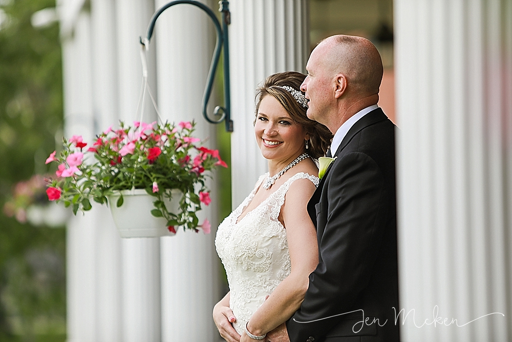 bride and groom standing on the porch of the country club in indiana county pa