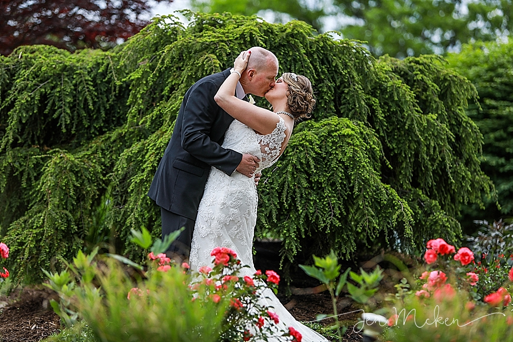 the groom dips his bride back for a kiss at the indiana county country club