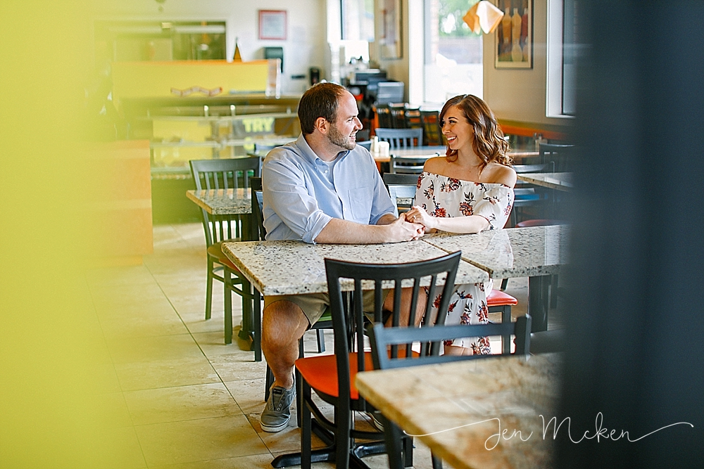 engaged couple sitting at restaurant tables inside of Romeo's Pizzeria & Mediterranean Kitchen where they met