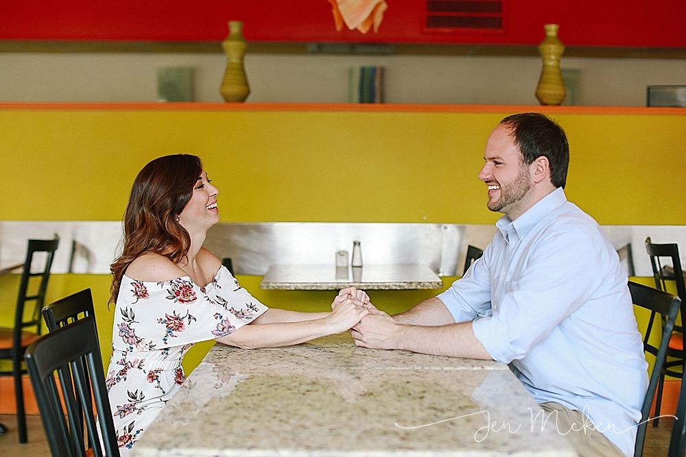 engaged couple holding hands over top of restuarant table of Romeo's Pizzeria & Mediterranean Kitchen where they met