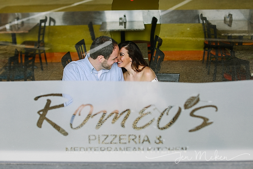 Engagement session at Romeo's Pizzeria & Mediterranean Kitchen thru the window at the table they first met