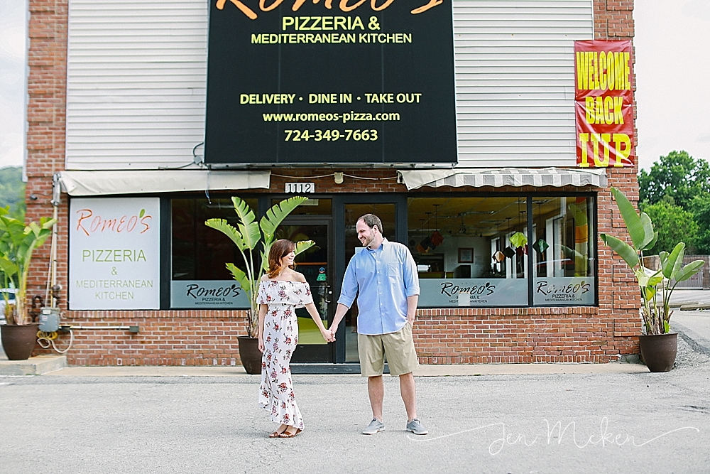 engaged couple standing outside of Romeo's Pizzeria & Mediterranean Kitchen in indiana pa on college campus