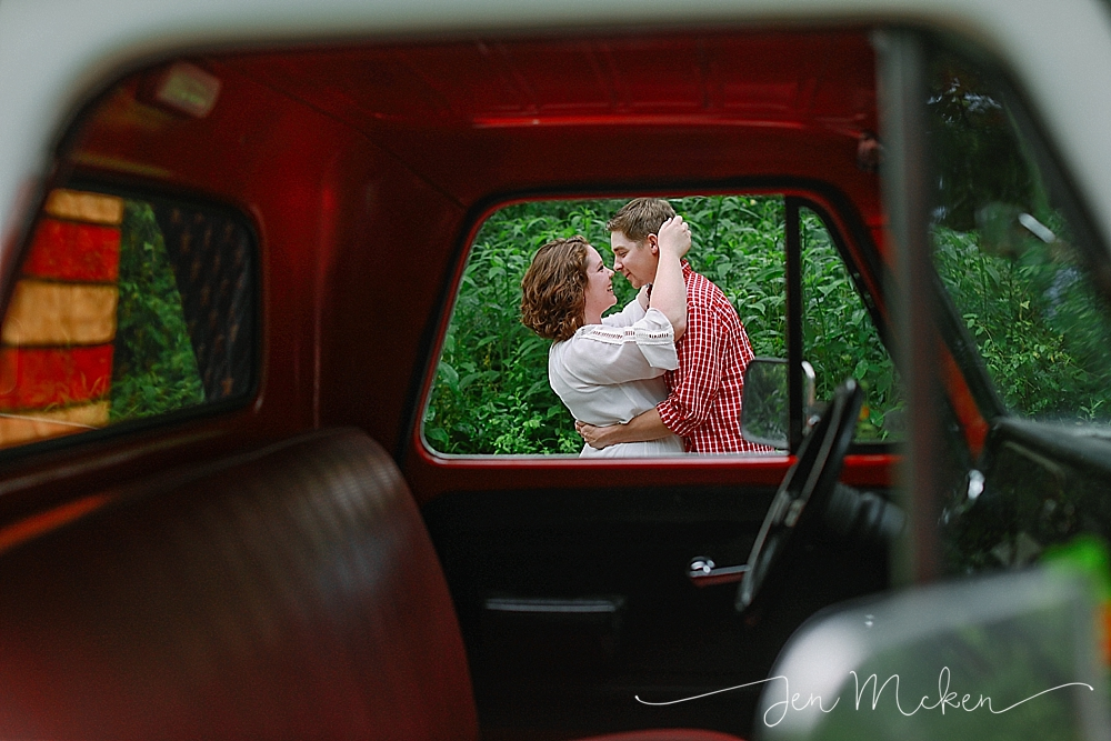 married couple kissing thru the window of a red 1968 chevy pickup