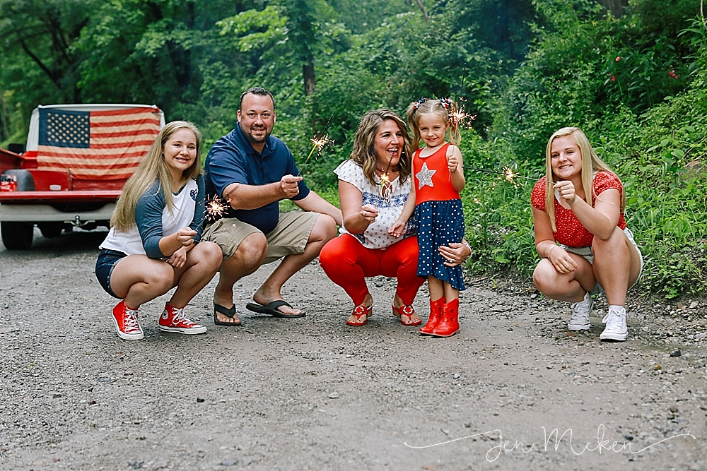 family shares smiles with 4th of july sparklers on a dirt road in indiana pa