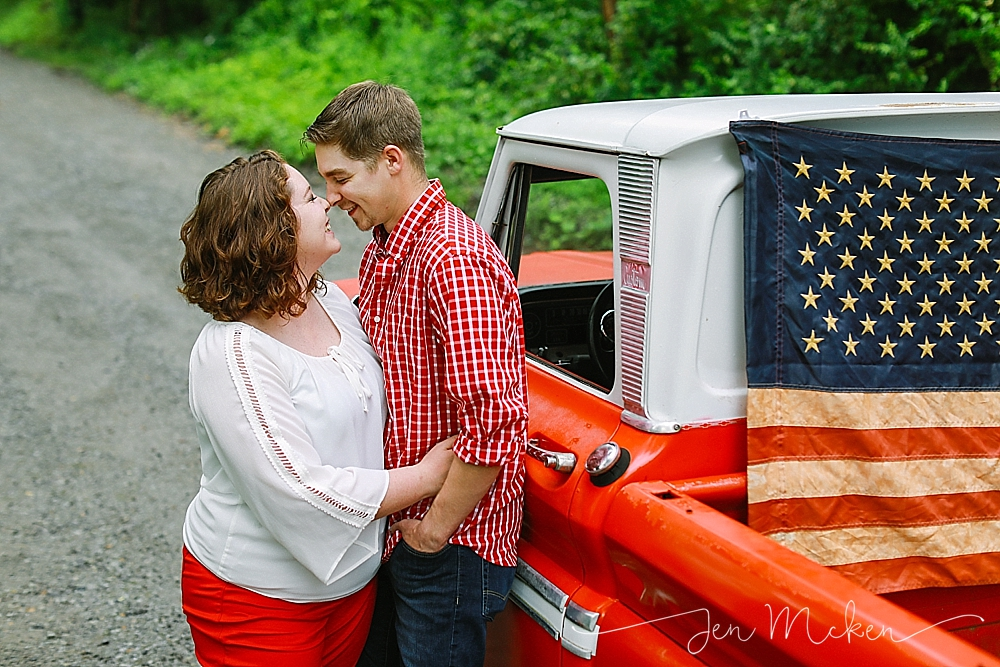 married couple kisses by the door of a 1968 chevy red pickup with an american flag on a dirt road in small town usa