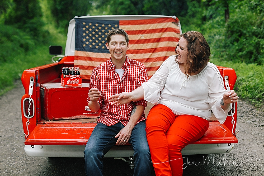married couple laughs while playing with sparklers on the back of a 1968 chevy on a dirt road