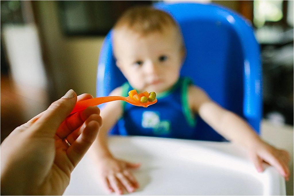 baby eating solid foods of peas and carrots