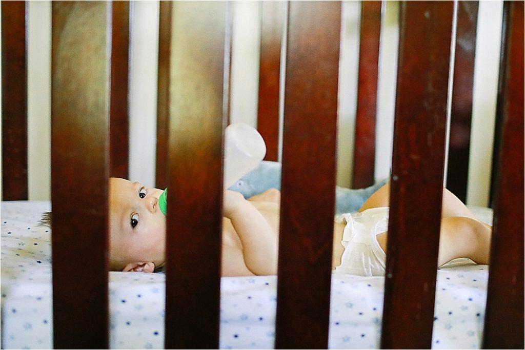 baby levi laying in his crib drinking a bottle