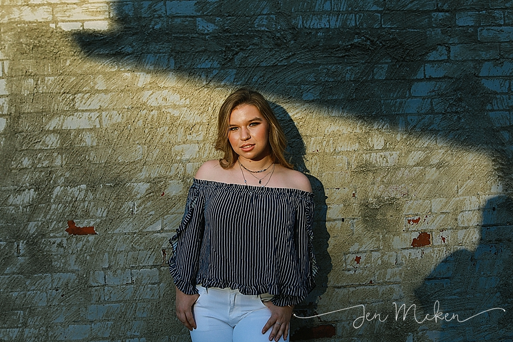 senior standing in a shadow for senior photos in the ally of indiana pa