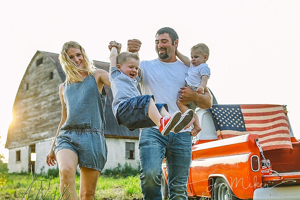 family tossing child in the air during their family photo session in small town pa