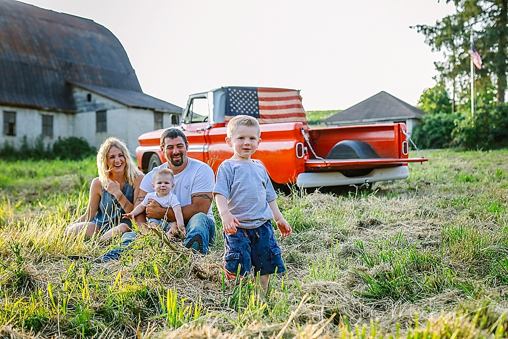 family sitting in a field with a vintage pick up truck and the american flag in blairsville pa