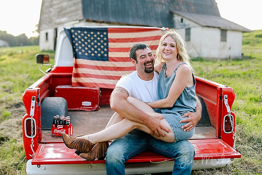 married couple laughing on the bed of a vintage pick up truck