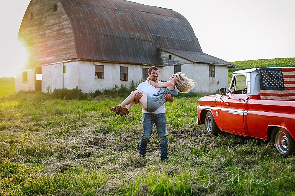 a married couple twirling in the field of a barn near a vintage truck