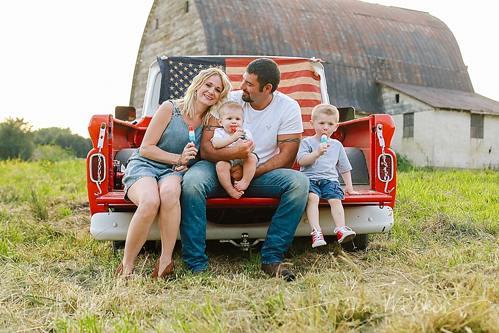 family sitting on the tailgate of a pickup truck