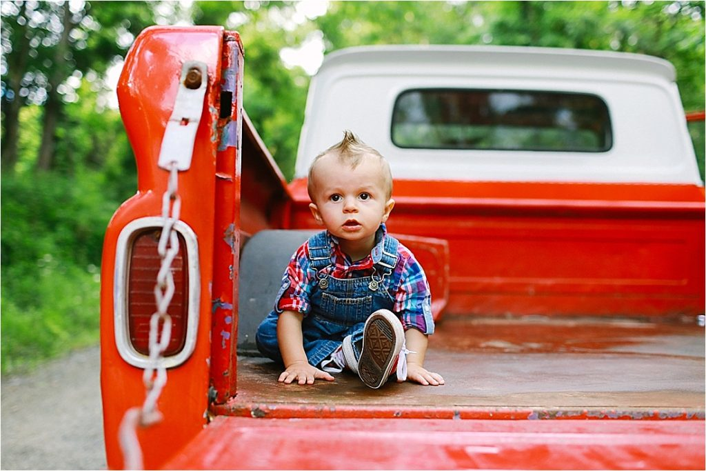 baby sitting in the bed of a 1968 red chevy pick up truck on a dirt road