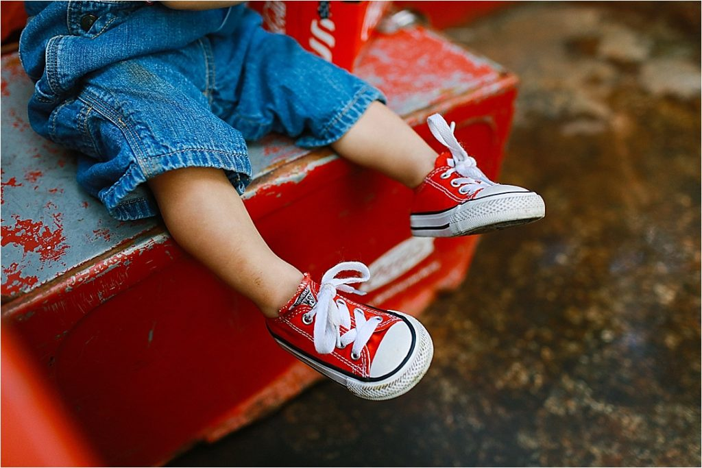 baby wearing red converse shoes
