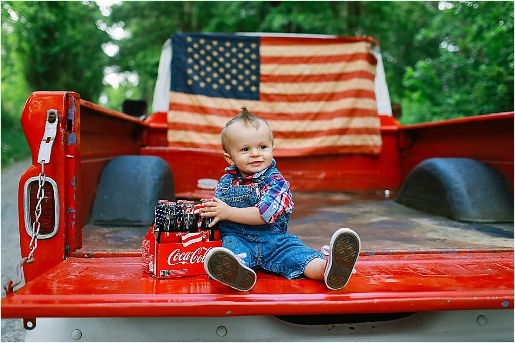 baby holding vintage coke bottles in front of an american flag