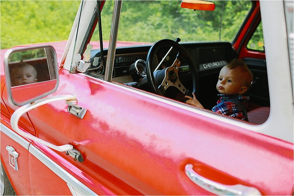 a one year old baby driving a vintage pick up truck down a dirt road in indiana county pa