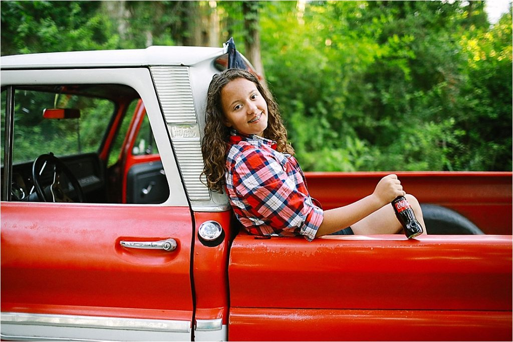 teenager hanging out in the truck bed holding a vintage coke bottle