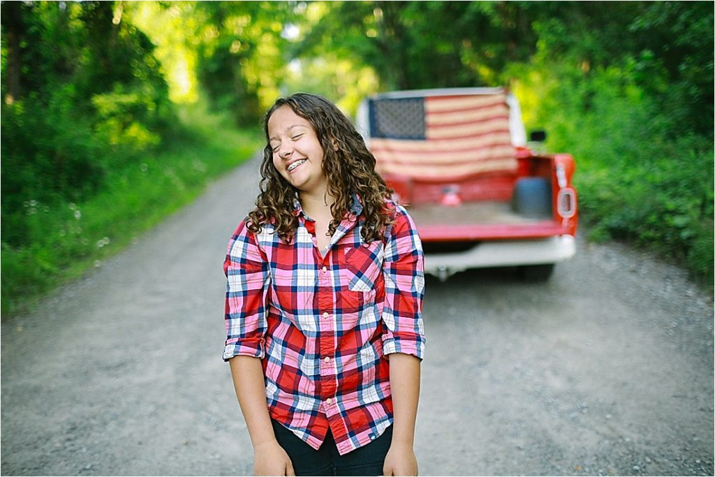 girl laughing on a dirt road in front of a red chevy pickup in small town usa