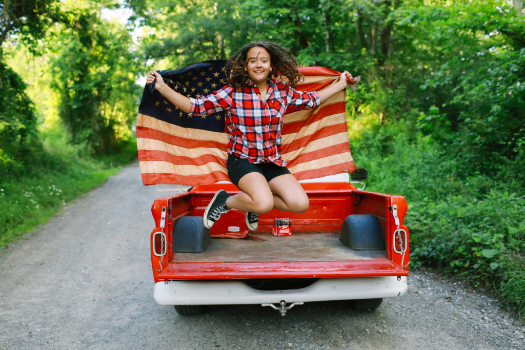 teen jumping off the truck with an american flag