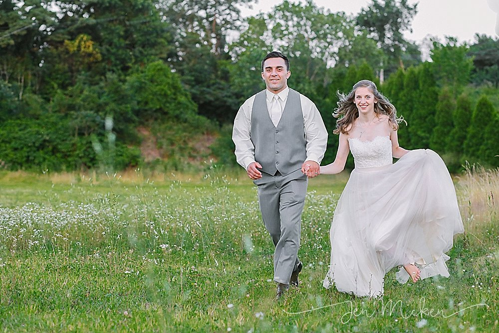 bride and groom running thru a field at veltres wedding and event center plum pa