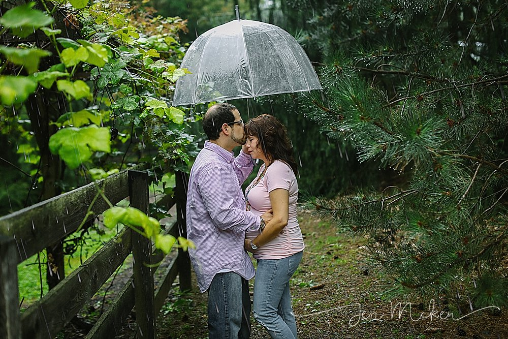 couple cuddling under the umbrella for their maternity session