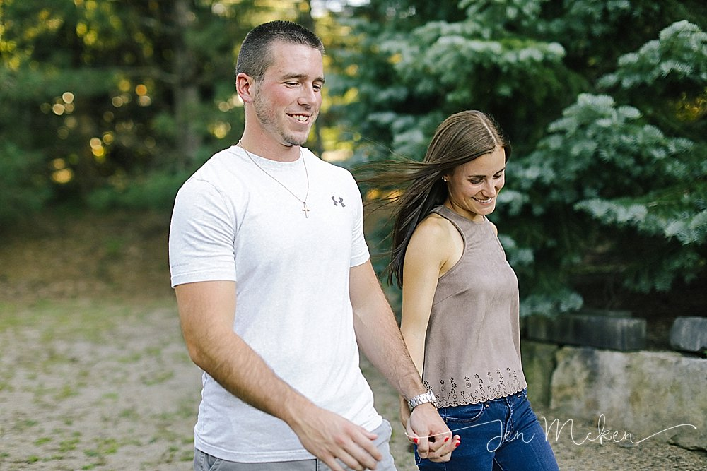 engaged couple holding hands and walking