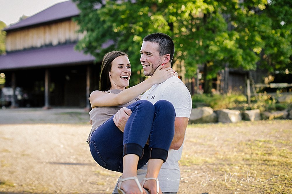 engaged couple laughing and twirling around near a barn in indiana county pa