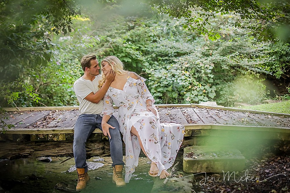 engagement session with white dress sitting on a wooden bridge