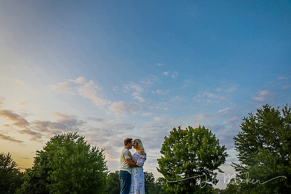 engagement photos in an open field with blue sky and sun surrounded by trees in rural pennsylvania