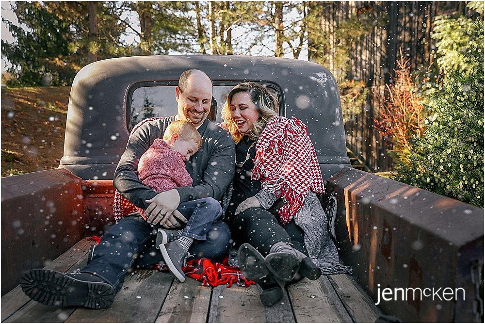 family sitting in the back of a 1950 rat rod truck for christmas photos during the winter