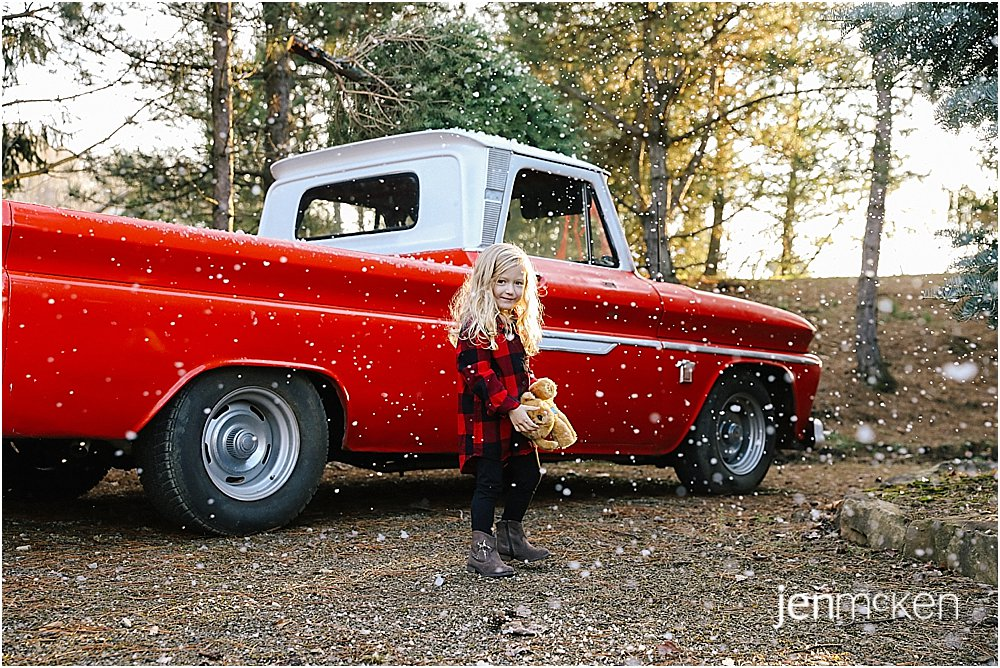 christmas family photos in the snow near a 1965 chevy red truck