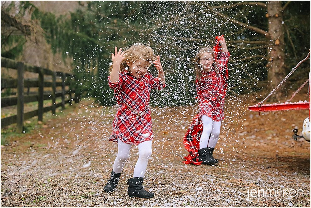 sisters dancing in the snow during their winter family photos