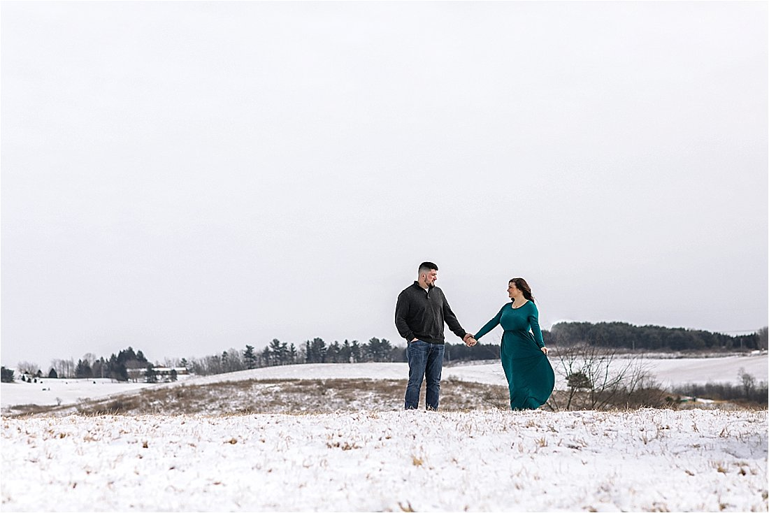 engaged couple on top of a hill in the snow with the wind blowing